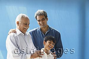 Asia Images Group - Grandfather, father, son laughing, blue background