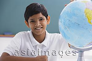 Asia Images Group - boy smiles at camera with globe