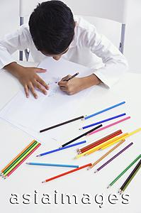 Asia Images Group - boy works with colored pencils (top view)