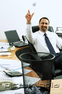 PictureIndia - Businessman sitting in office throwing paper ball into dustbin, smiling